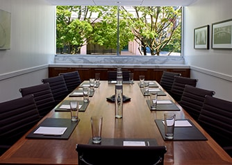 boardroom with large window and place settings of notepads and water glasses