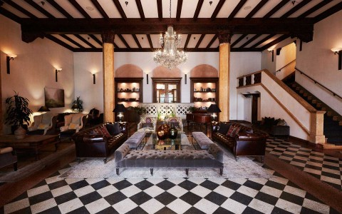 Lobby area with checkered flooring, leather couches and fireplace