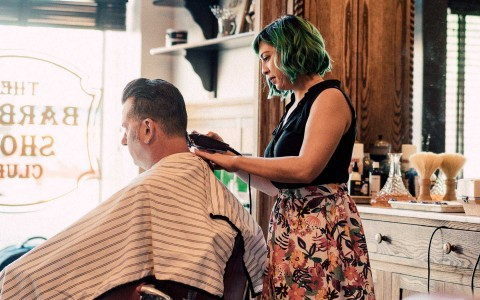 Woman cutting mans hair in barber shop