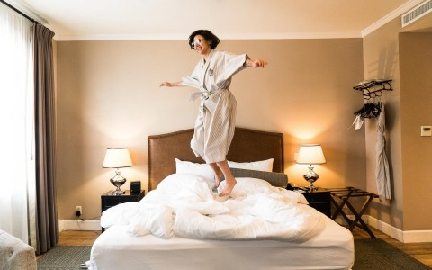 Woman in robe jumping on bed