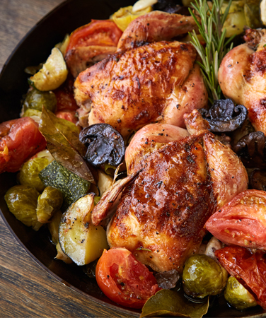 roasted chicken with tomatoes, mushrooms, zucchini, and herbs in a cast iron skillet sitting on a wooden table