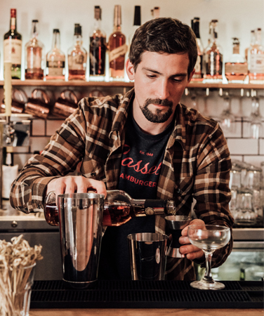 a bartender making a cocktail behind a bar