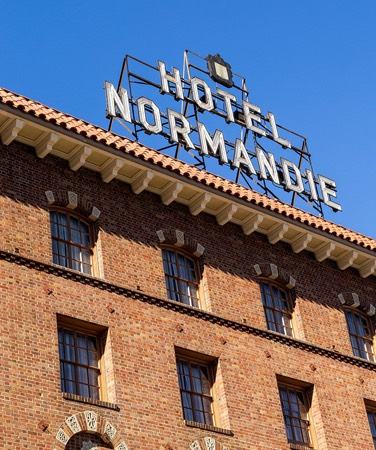 hotel normandie sign at the top of brick building