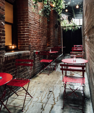 outdoor seating with red tables and chairs next to brick walls