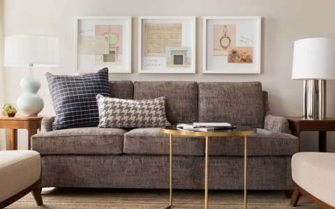 gray sofa with pillows and three pictures hanging on the wall behind it
