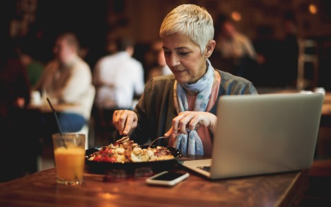 woman with a laptop eating dinner at a table
