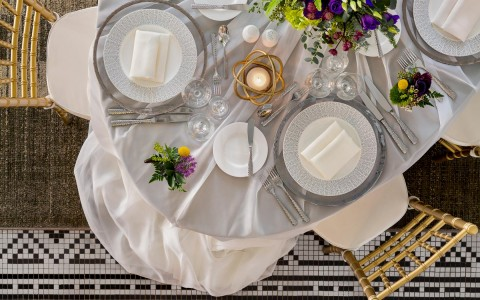 round table set up for an event with white linen, flowers, candle, and plates