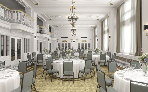 reception room set up with round white table cloth tables and gray chairs with an indoor balcony on the second floor