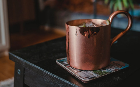 copper mug on a coaster on a black table