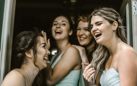 group of bridesmaids laughing together with the bride