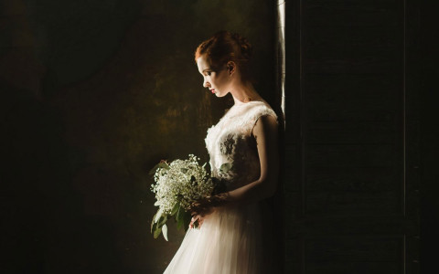 a light shines on a bride looking down at her flower bouquet in a dark room