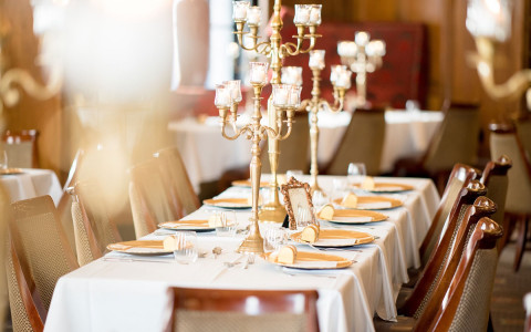 elegant wedding reception dining table with gold candlestick centerpieces on tables