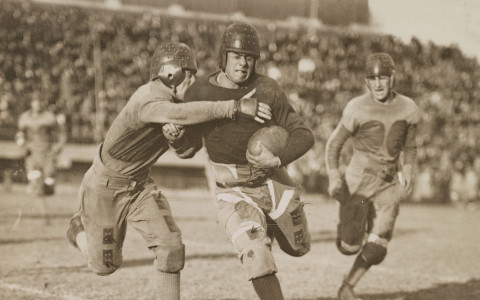 black and white antique image of a football player being tackled in a game