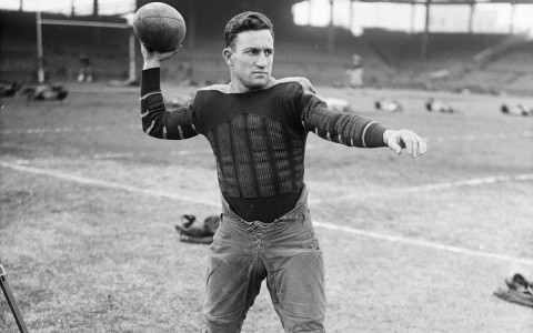 black and white image of a man throwing a football at practice