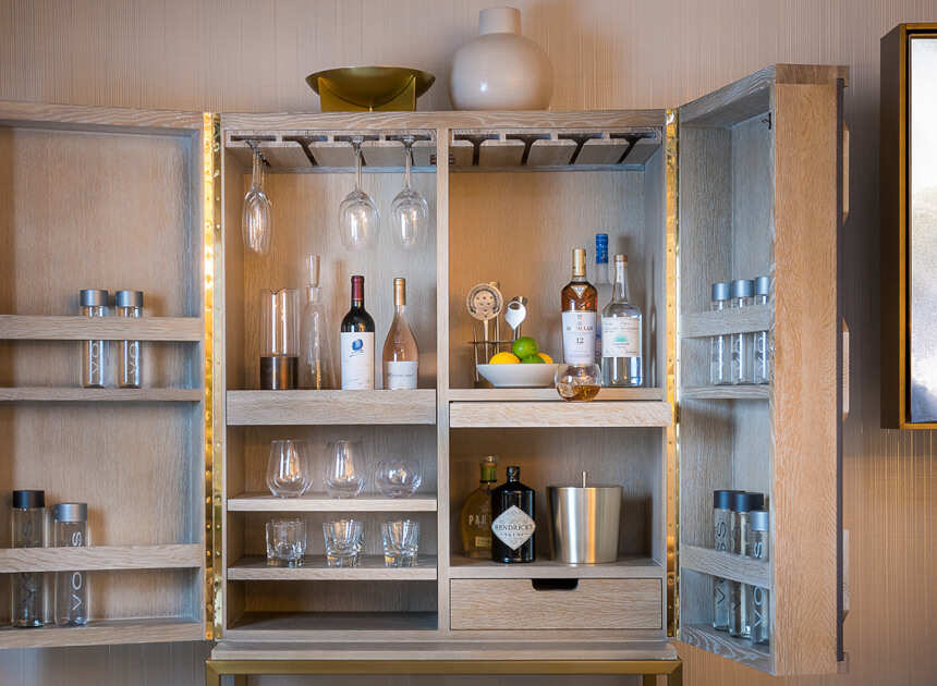 an open bar cabinet with empty cocktail glasses and various bottles of alcohol