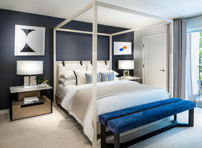 guest room with a blue patterned wall, white linen bed with a white bed frame, blue bench, nightstands and balcony
