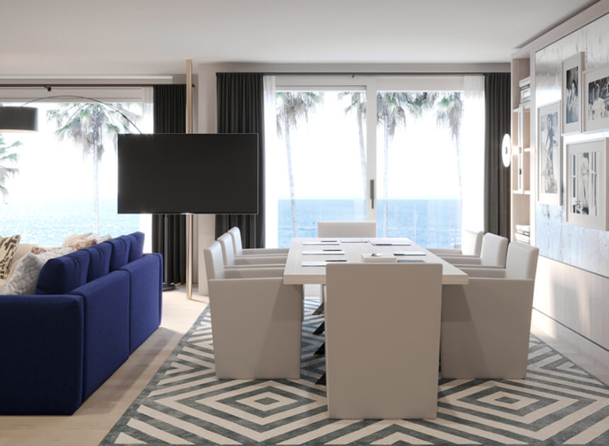 dining room table overtop a patterned rug with a view of the ocean