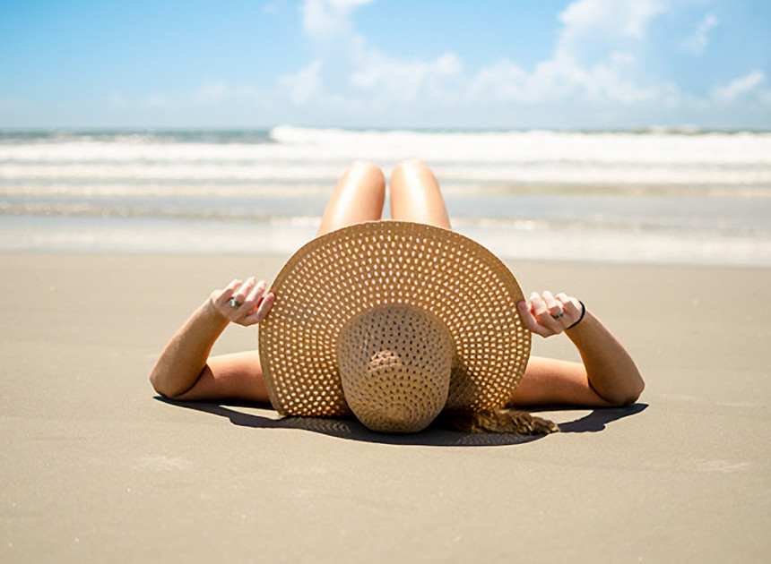 woman wearing a wide brim sun hat laying on the beach