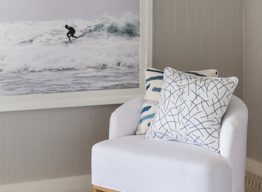 white chair on blue carpet next to photo of surfer