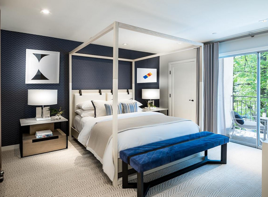 bedroom with a patterned blue wall, white linen bed in a white bed frame, blue bench, and two nightstands with lamps
