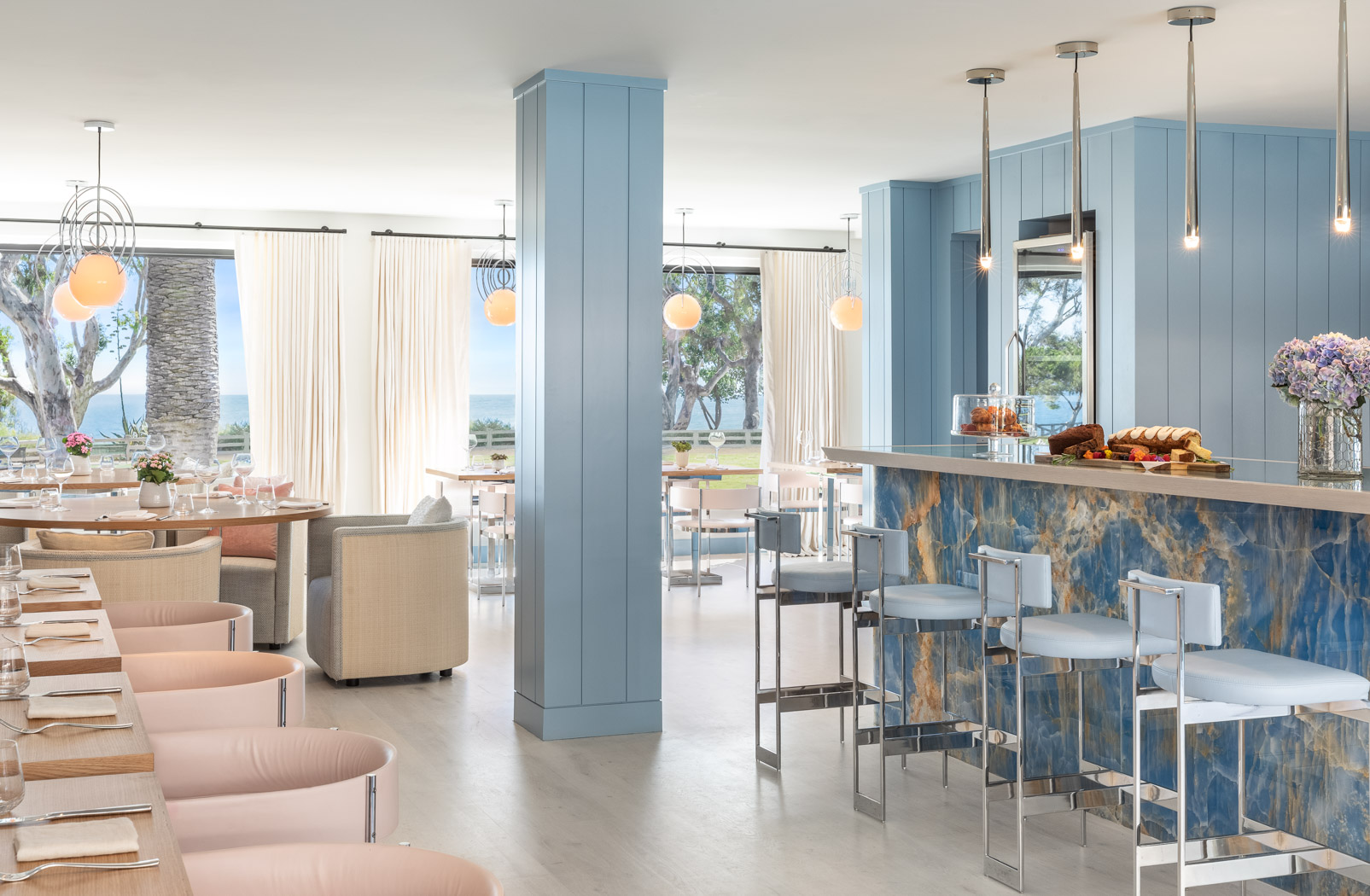 blue dining area with a bar and barstools and large windows
