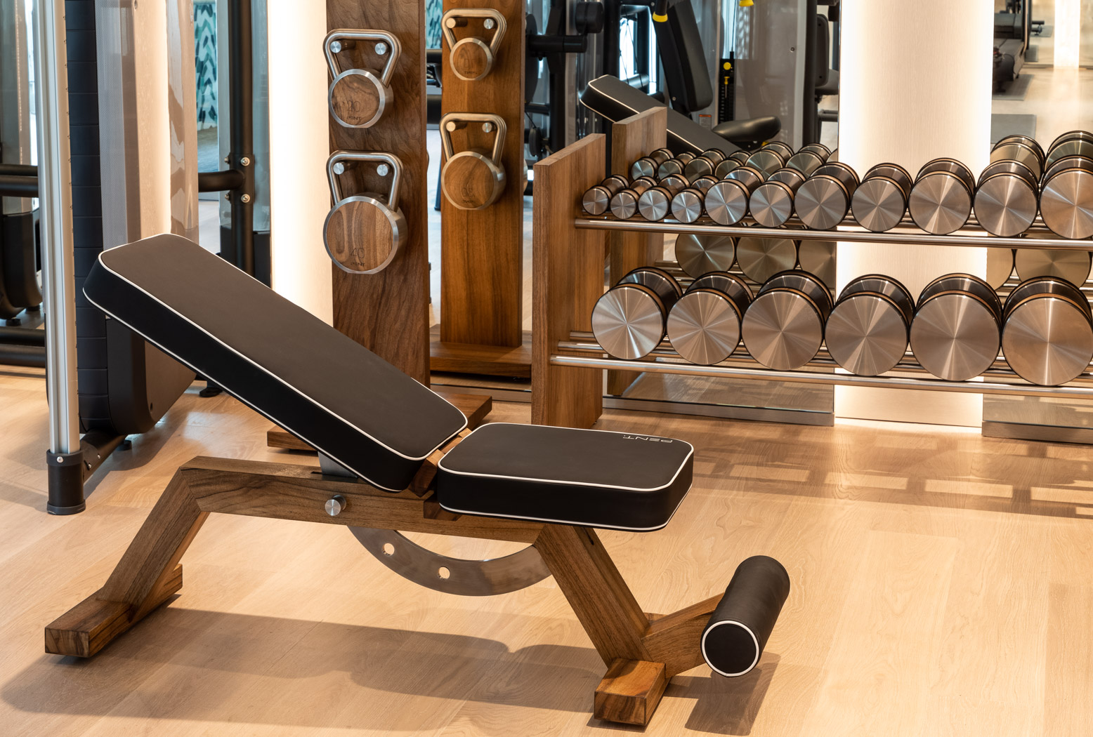 a gym with a bench and silver dumbbells