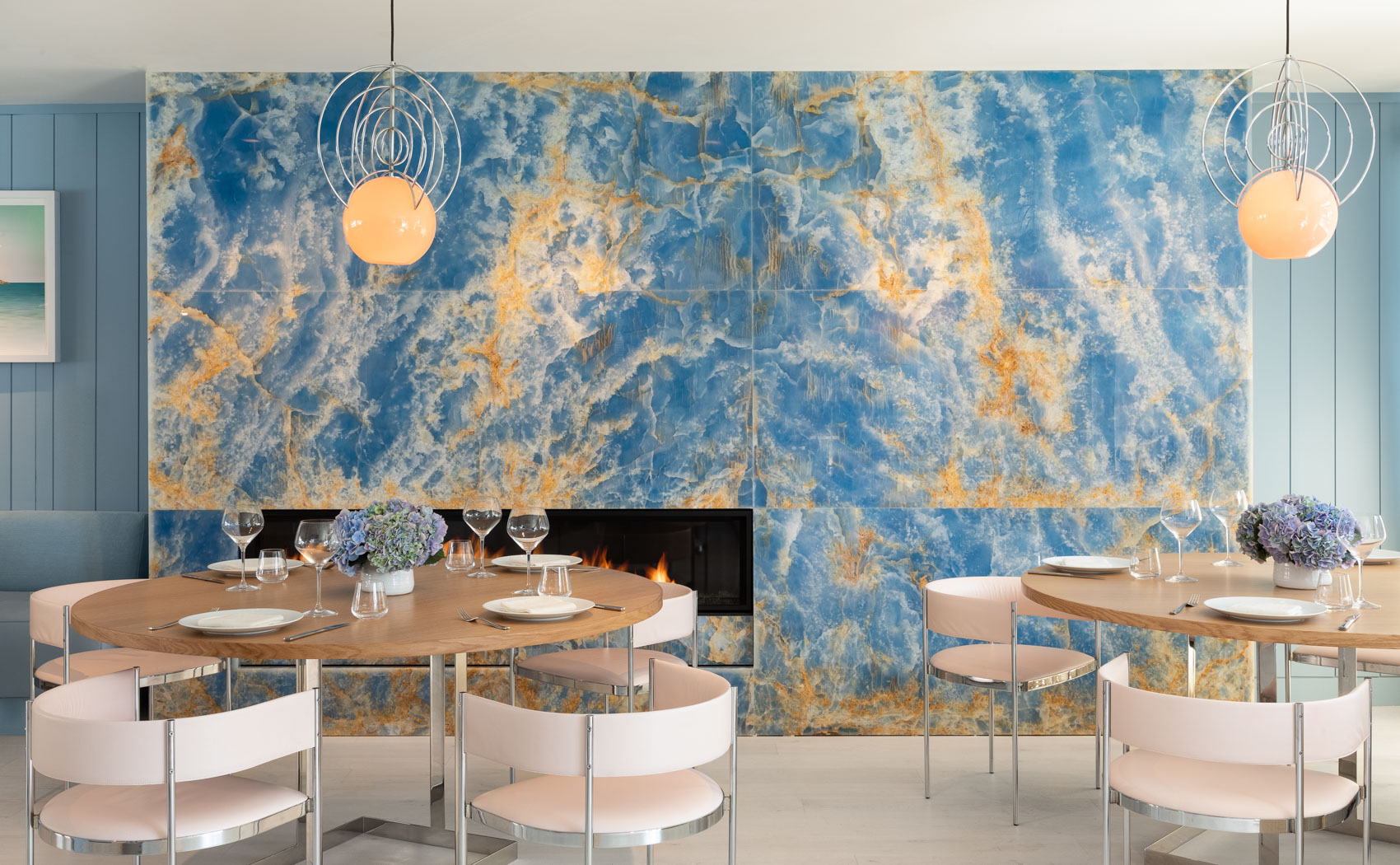 a dining area with a blue and yellow marble wall and two tables