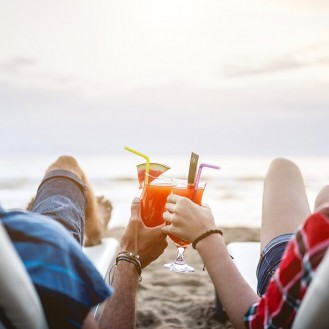 two people toasting with fruit cocktails on the beach