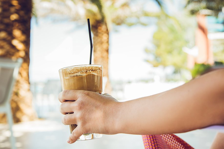 hand holding an iced coffee drink