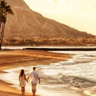 couple holding hands walking down beach