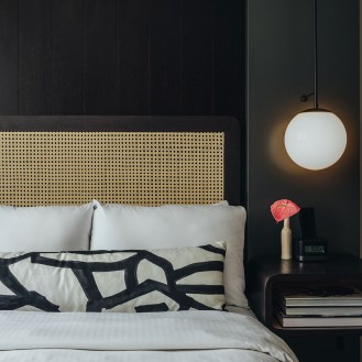 guest bed with wicker headboard and black and white pillow