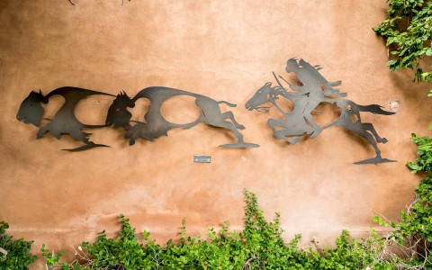 metal artwork of native american chasing buffalos