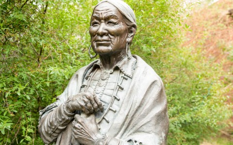 statue outside of old woman native american