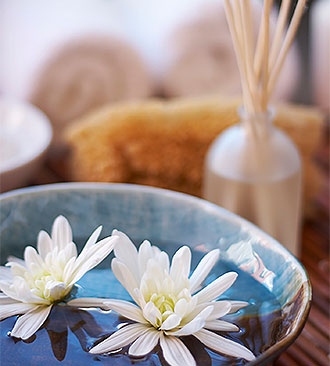 bowl with flower heads floating in water with towels and room scent diffuser in background