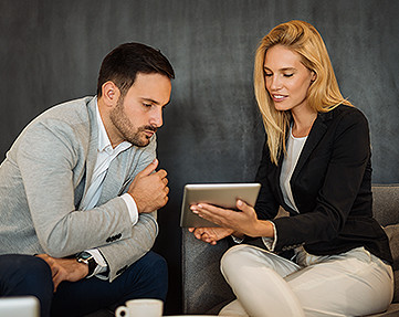 business man and woman looking at an iPad