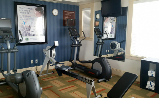 Fitness room with elliptical, row machine, another elliptical and a mirror