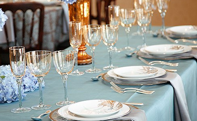 elegant table setup with blue tablecloth and silver napkins