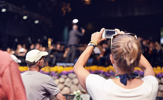 woman taking a picture of a person on a stage