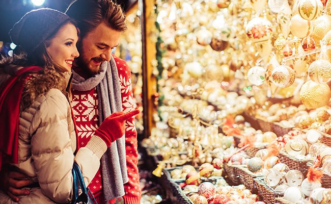 couple looking at shiny christmas ornaments