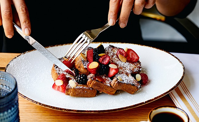 person cutting into a french toast dish topped with fresh fruit