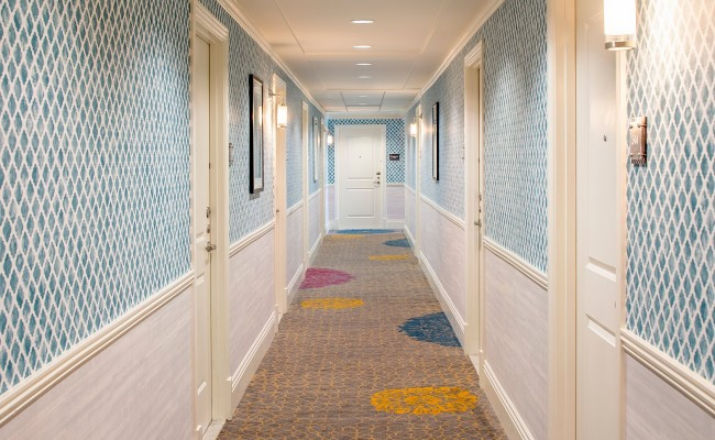 View of hotel rooms hallway with blue tiled walls and carpet with yellow blue and pink circles