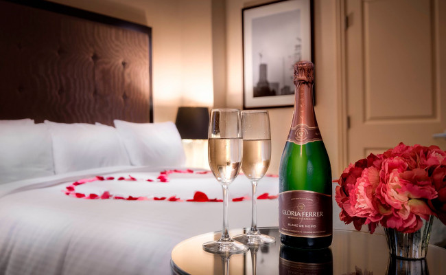 rose petals in the shape of a heart on a bed with two glasses of champagne on a table