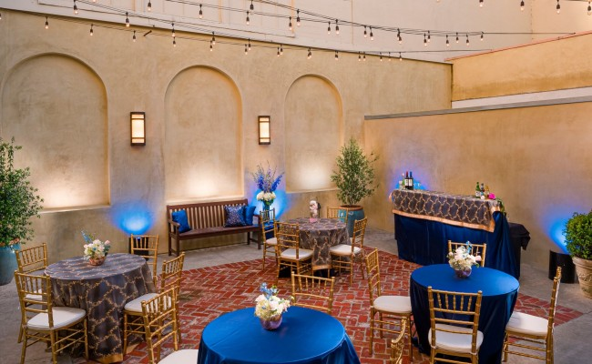 Wedding venue setup with blue tablecloth round tables and gold chairs