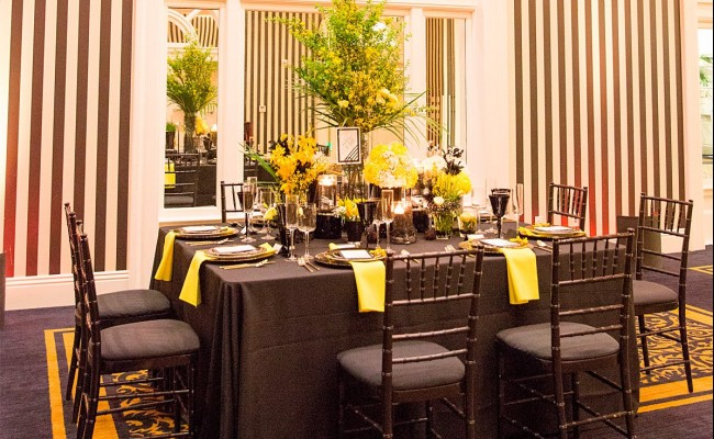 Wedding venue setup with black tables and chairs, yellow flowers and yellow napkins