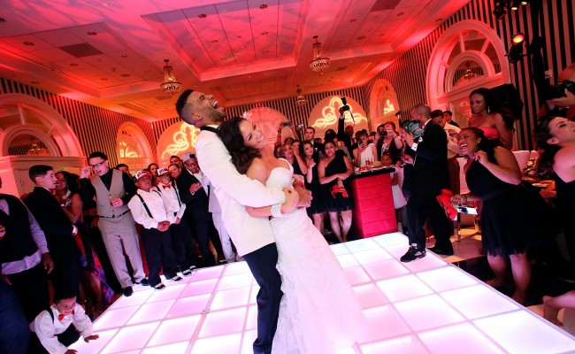 Bride and groom laughing on the dance floor at a wedding surrounded by guests