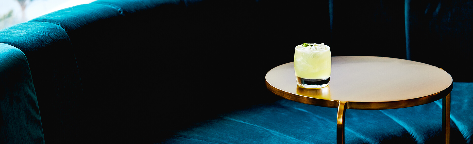 a cocktail on a gold side table next to a couch