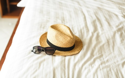 hat and sunglasses on bed