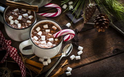 Candy Canes in hot cocoa with marshmellows on table