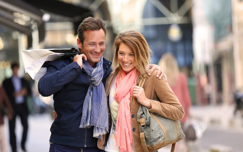 smiling couple in scarfs with shopping bags