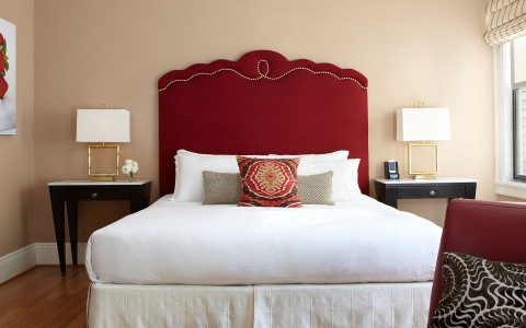 bed with red headboard and  white bedding
